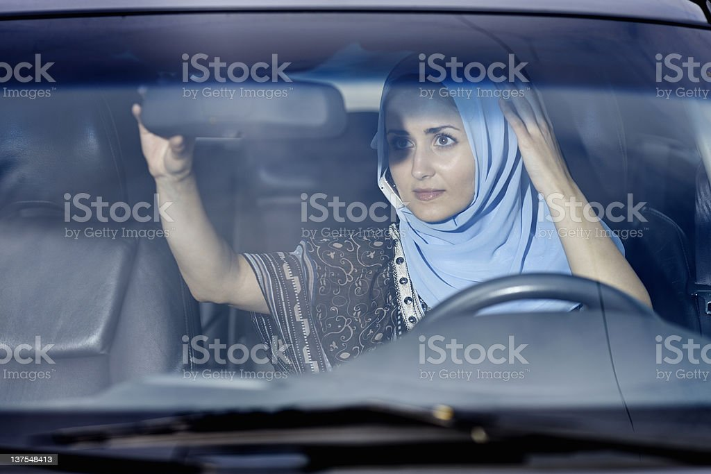 Woman in headscarf checking mirror stock photo
