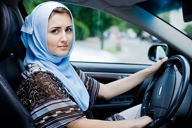 Woman in headscarf driving stock photo