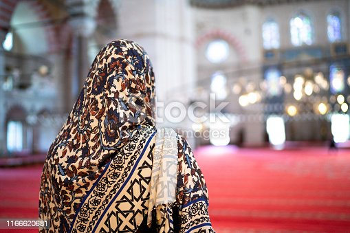 Woman in headscarf praying in a Mosque