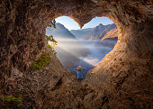 istock Woman in heart shape cave watching the misty canyon at morning 873620314