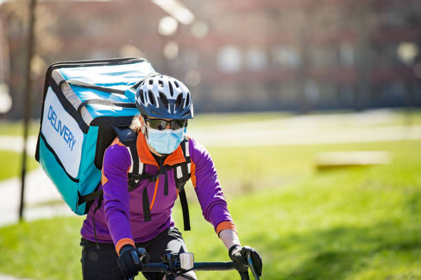 Woman in helmet and protective mask with big food delivery backpack riding bike stock photo