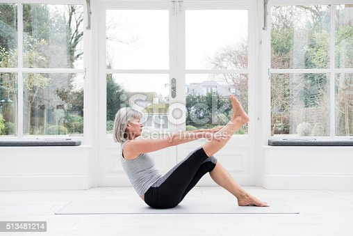 Senior woman sitting on floor with one leg raised and stretching. She is in the conservatory practicing yoga and pilates, keeping fit and exercising.