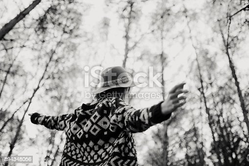 istock Woman in her back enjoying nature, with opened arms. Forest trees background and black and white tone. 894348056