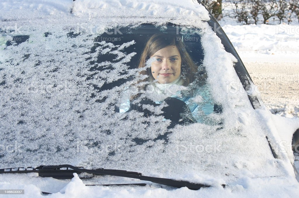 A woman in her car with snow covering her windshield stock photo