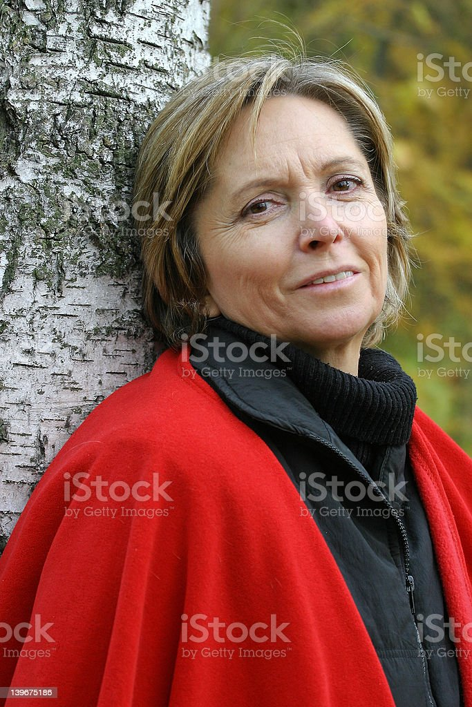 woman in her fifties standing by the tree royalty-free stock photo