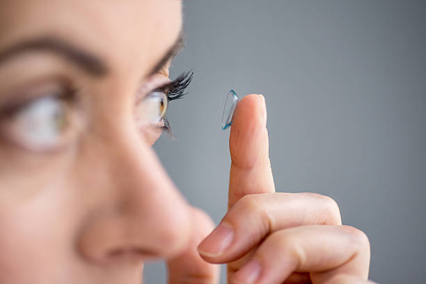 woman in her forties inserting contact lenses stock photo