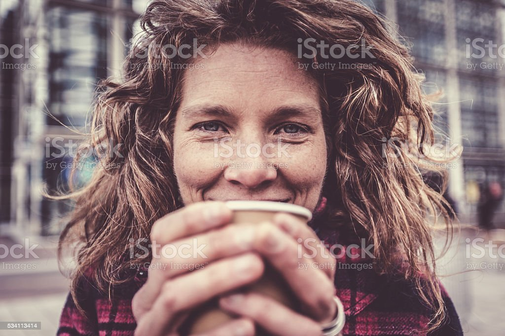 Woman in her forties warming her hands on coffee cup stock photo
