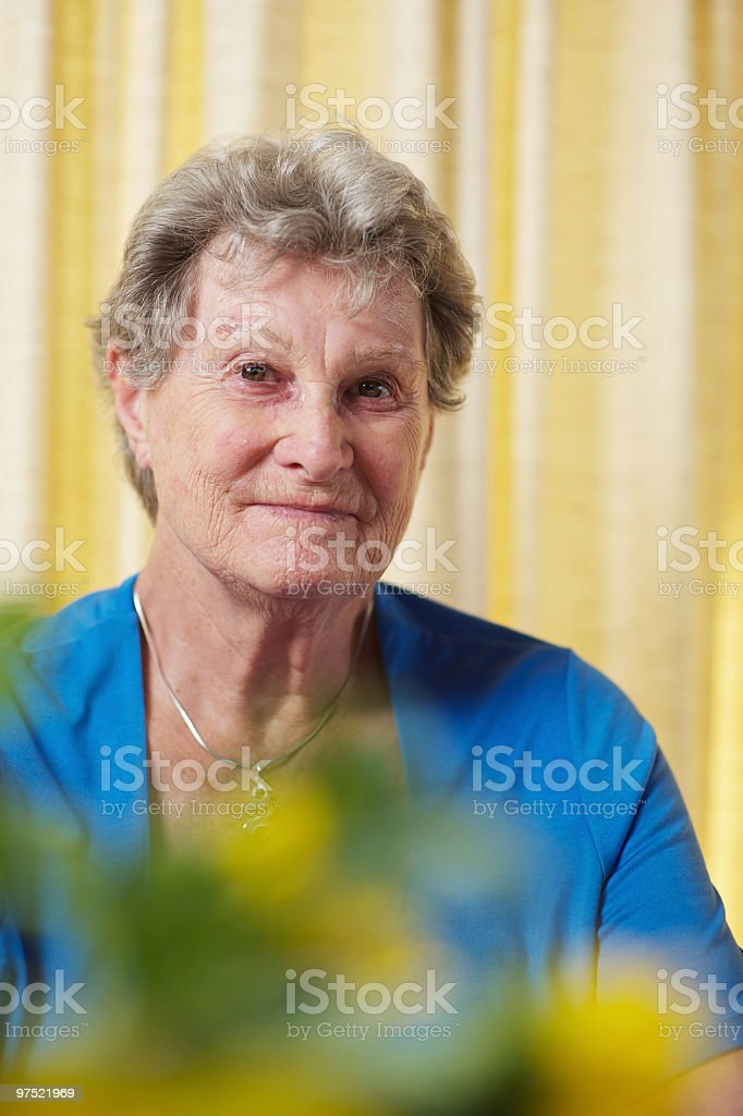 Woman in her mid-seventies looking at the camera shot vertically royalty-free stock photo