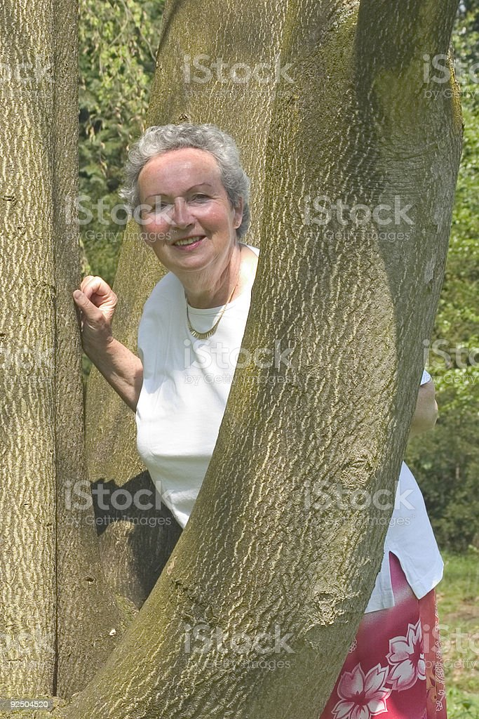 Woman in her sixties looking around a tree royalty-free stock photo