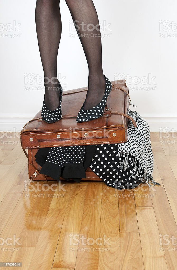 Woman in high heel shoes standing on overfilled suitcase royalty-free stock photo