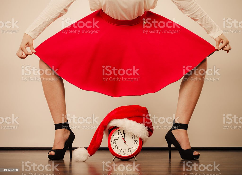 Woman in high heels with alarm clock. Christmas. stock photo