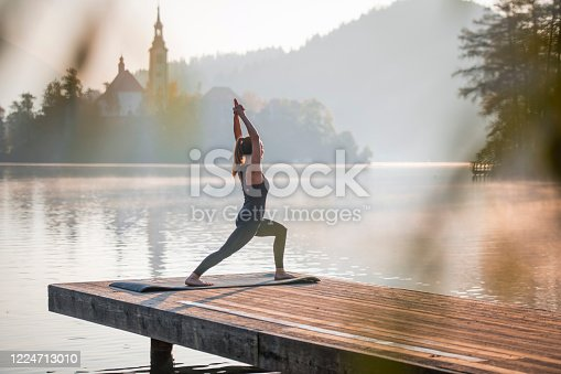 Mid distance view of Caucasian woman in early 30s standing on pier overlooking Lake Bled in yoga High Lunge Position (Utthita Ashwa Sanchalanasana).