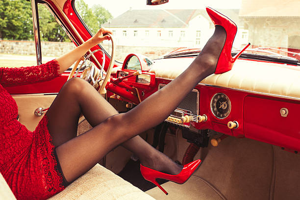 Woman in high-heals sitting in retro car - Photo