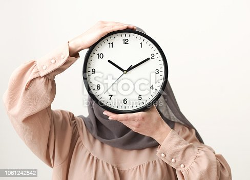 istock Woman in hijab covering face with clock 1061242842