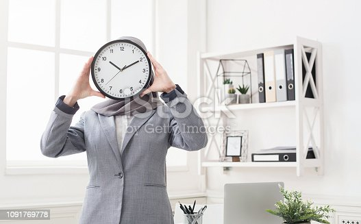 istock Woman in hijab covering face with clock 1091769778