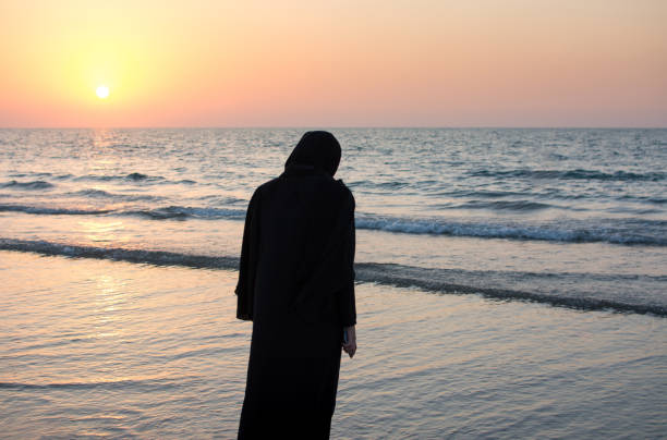 Woman in hijab standing on the beach stock photo