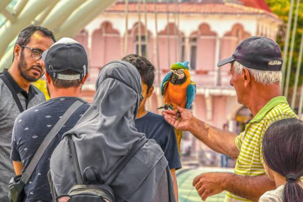 frau in hijab mit niedlichen rucksack mit ohren und sonnenbrille - mann sprach ernsthaft mit einem anderen mann, während ältere mann und junge mädchen bewundern einen papagei, dass junge mann auf der schulter hat - urbanara stock-fotos und bilder