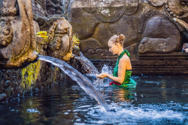 woman in holy spring water temple in bali. the temple compound consists of a petirtaan or bathing structure, famous for its holy spring water - традиционная церемония стоковые фото и изображения