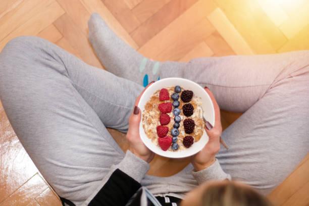 Femme en vêtements maison manger la bouillie d'avoine dans un bol orné de mûres, framboises et bleuets - Photo