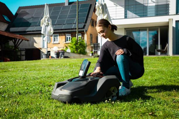 Woman in Home Garden programming Robotic Lawn Mower stock photo