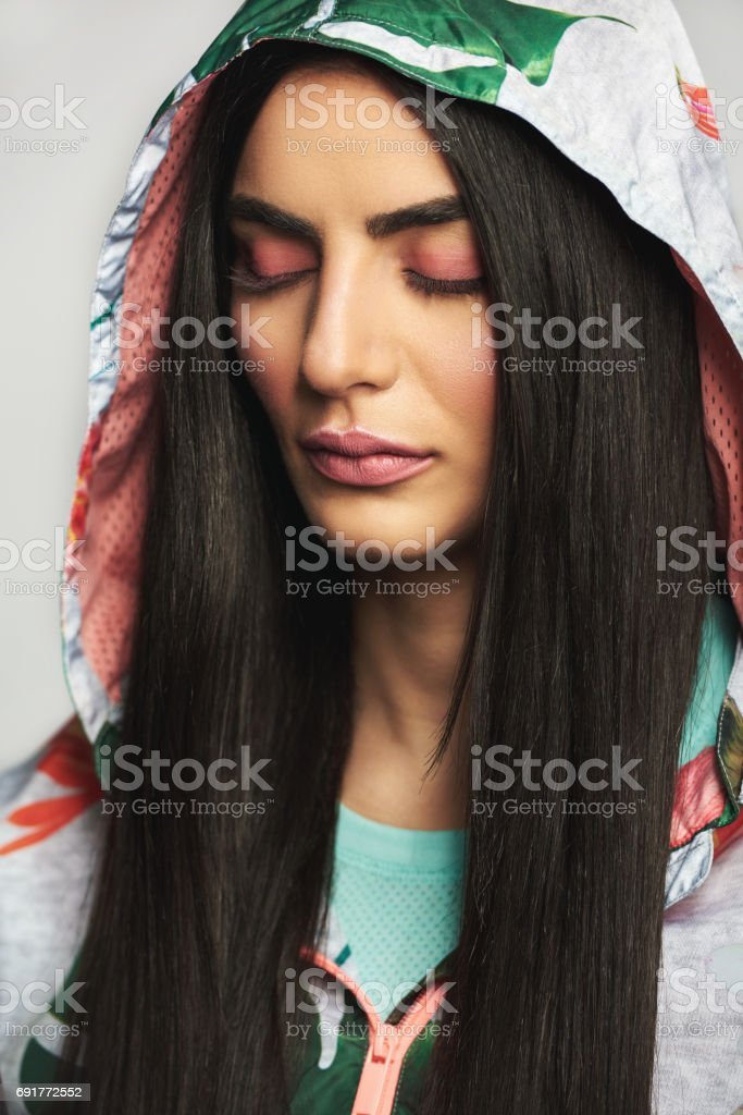 Woman in hood with eyes closed stock photo