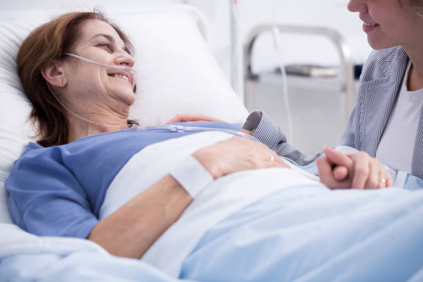 Woman in hospital with volunteer Ill, smiling woman in the hospital bed with volunteer chemotherapy cancer stock pictures, royalty-free photos & images