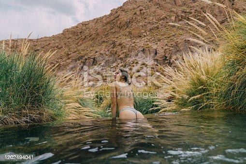 Young Caucasian woman swimming  in hot spring in Atacama desert