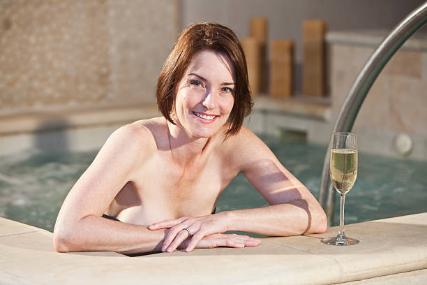 woman in hot tub, drinking champagne - older women bikini stock pictures, royalty-free photos & images