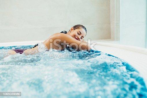 Beautiful young woman enjoying and relaxing in SPA hot tube.