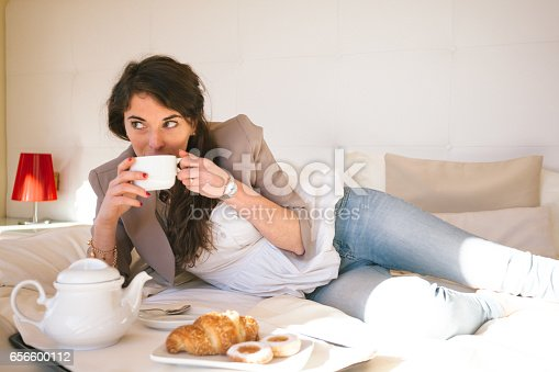 istock Woman in Hotel Bedroom having breakfast 656600112