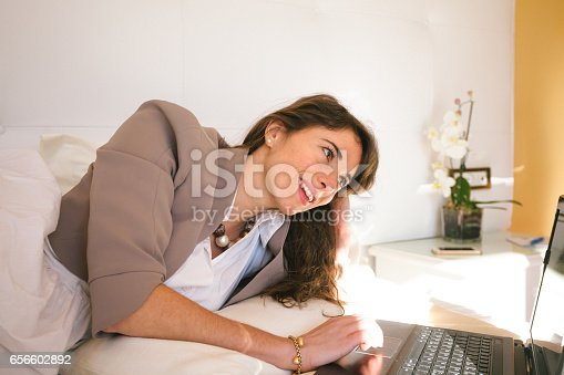 istock Woman in Hotel Bedroom using Laptop 656602892