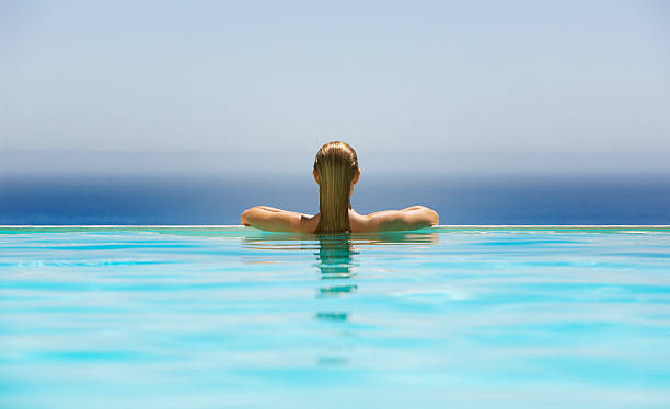 Woman in infinity pool stock photo