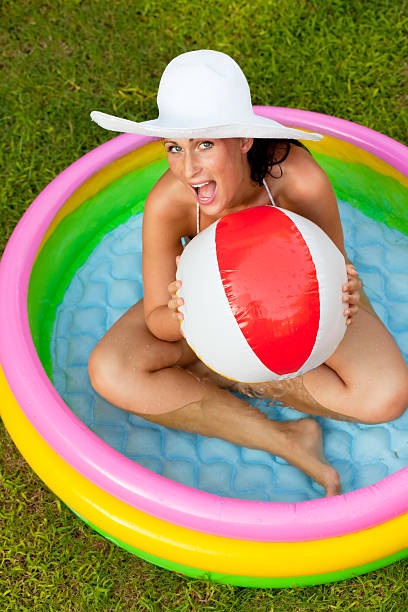 woman in inflatable pool with waterball stock photo