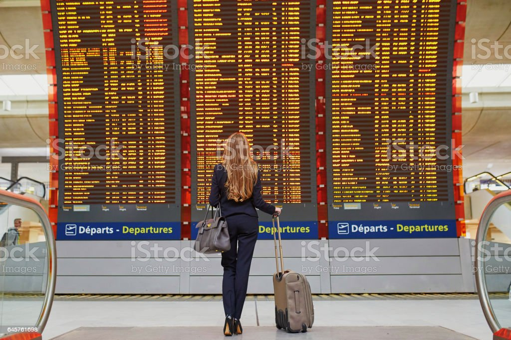 Woman in international airport terminal, looking at information board stock photo