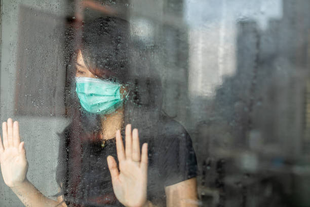 woman in isolation at home for virus outbreak or hypochondria Young woman in isolation at home for coronavirus  looking out of window during rain avoidance stock pictures, royalty-free photos & images