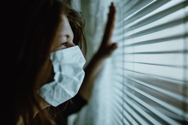 donna in isolamento a casa per l'epidemia di virus - hand on glass covid foto e immagini stock