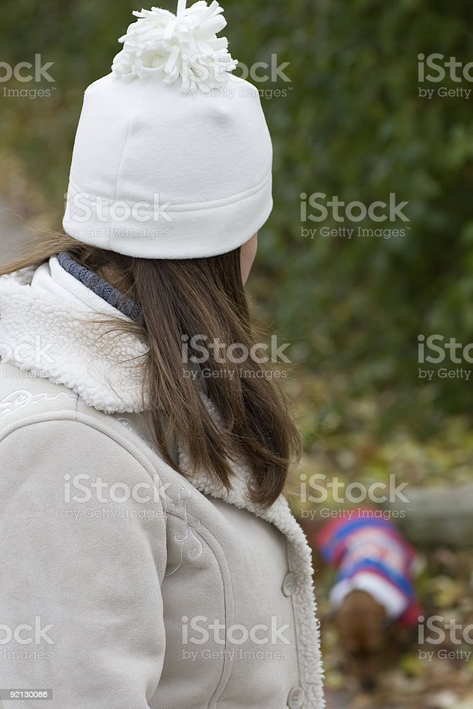 Woman in jacket and hat looking back at small dog. royalty-free stock photo