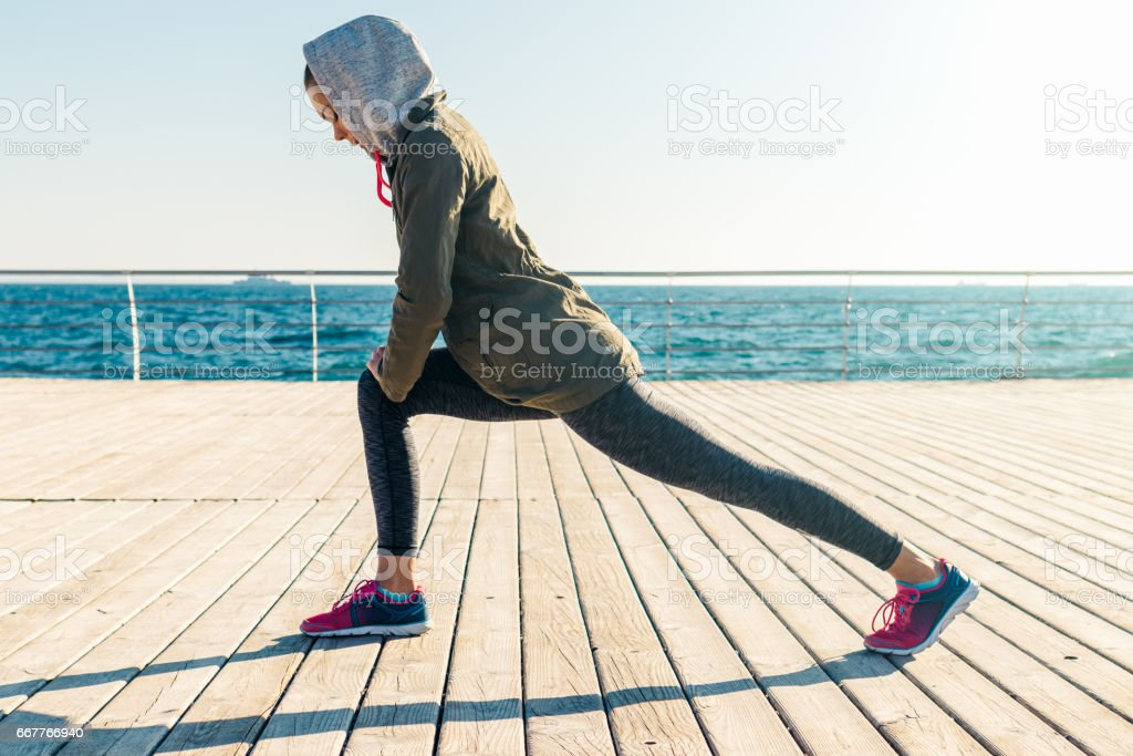 Woman in jacket and hood doing sports exercises on the beach in the morning stock photo