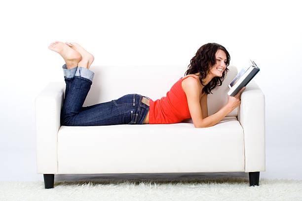 Frau liest ein Buch auf dem Sofa – Foto