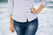 Woman in jeans and shirt standing in the sea foam