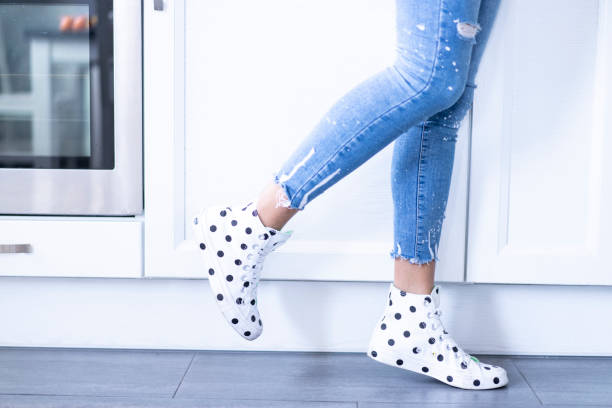 Woman in jeans and sneakers with dots walking in kitchen stock photo