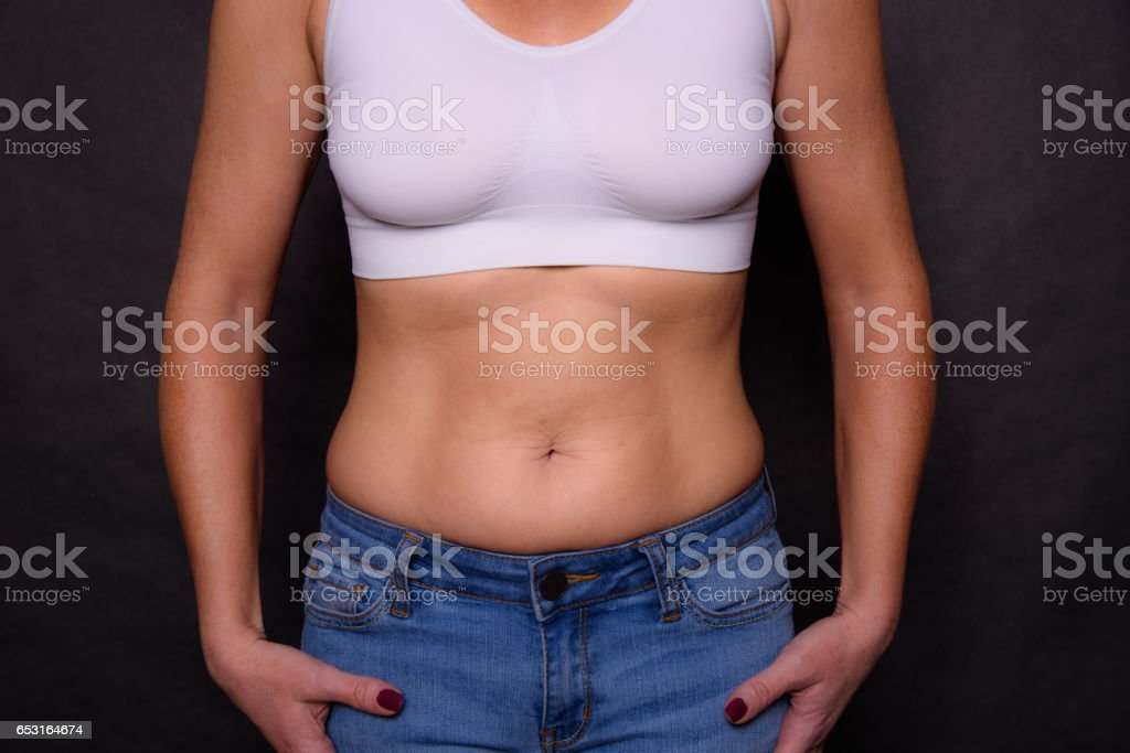 A Woman In Jeans and Sports Bra with Some Belly Bulge stock photo