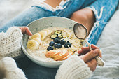 Woman in jeans and sweater eating healthy oatmeal porriage
