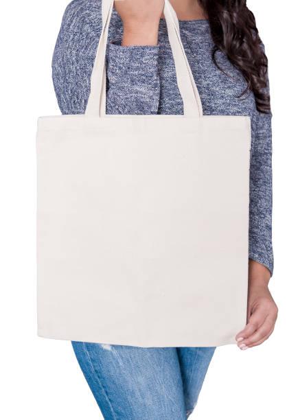 frau in jeans leer stofftasche isoliert halten. mock-up für design - leinenhosen frauen stock-fotos und bilder