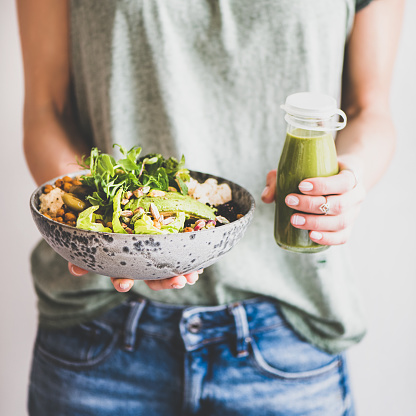 Woman in jeans holding healthy championship game and smoothie, square crop