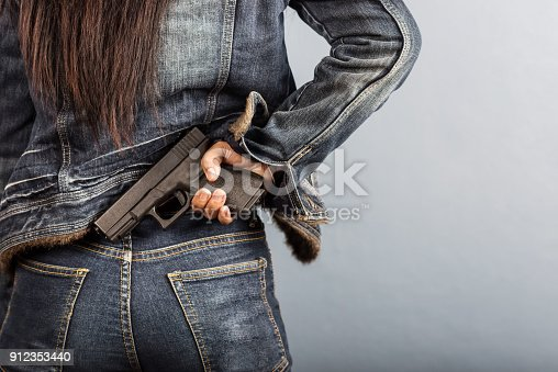 istock Woman in jeans is holding a gun in her hand. 912353440