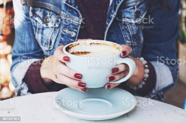 Woman in jeans jacket holding cup of cappuccino in her hands with red picture id867337924?b=1&k=6&m=867337924&s=612x612&h=demxrveyxgniqmcwtqmov37xenomenvicz0apolucwg=