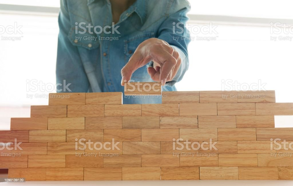 Woman in jeans shirt holding blocks wood game Building a small brick...