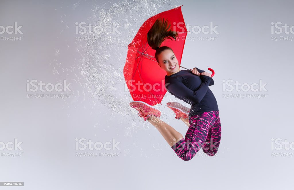 Woman in jump with an umbrella. stock photo
