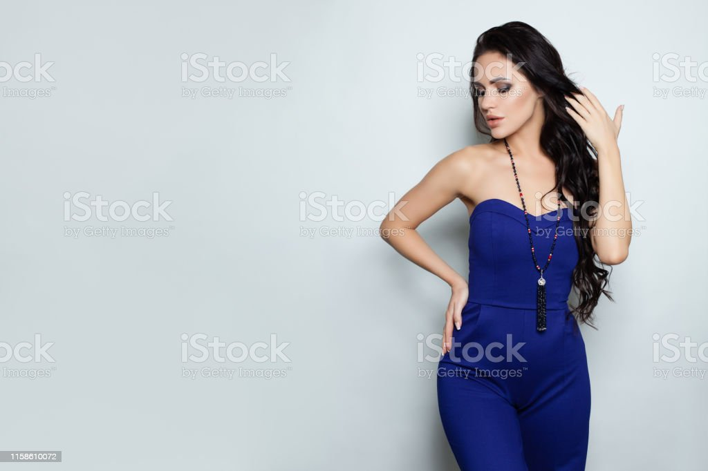 Woman in jumpsuit posing against white wall background. Fashion model...